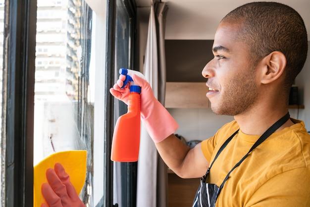 Governanta limpando janela de vidro em casa