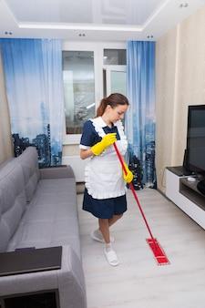 Governanta limpando uma suíte de hotel esfregando o chão entre um sofá confortável e uma televisão na parede