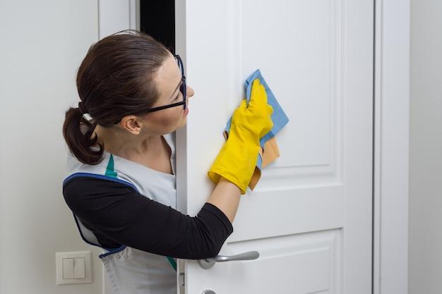 Governanta mulher limpa a porta com pano