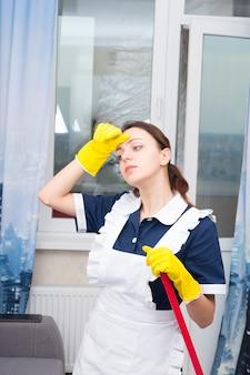 Governanta ou empregada doméstica cansada e quente em pé segurando um esfregão ou vassoura, enxugando a testa com a mão enluvada, vista de perto