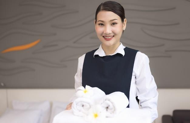 Governanta segurando toalhas em um hotel, jovem camareira com toalhas limpas no quarto, serviço de quarto perfeito