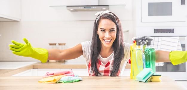 Governanta sorridente com os braços bem abertos na cozinha, com trapos coloridos e detergentes sobre a mesa.