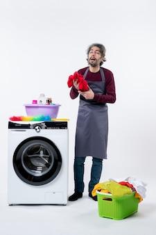 Governanta, vista frontal, homem, com os olhos fechados, segurando uma toalha vermelha em pé perto da máquina de lavar, no fundo branco