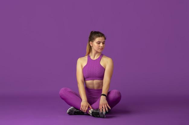 Graça. bela jovem atleta praticando, retrato roxo monocromático. modelo de ajuste caucasiano desportivo posando confiante. musculação, estilo de vida saudável, conceito de beleza e ação.