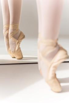 Graça e perfeição. close das pernas de bailarina em chinelos em pé contra o espelho