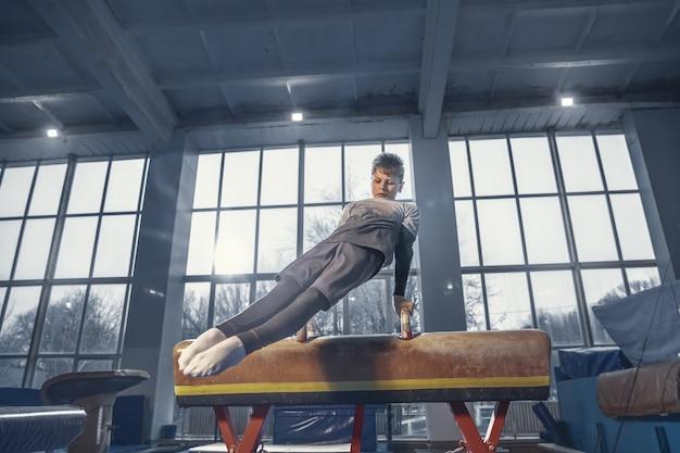 Graça. pequeno ginasta masculino treinando no ginásio, flexível e ativo. menino caucasiano, atleta em roupas esportivas, praticando em exercícios para força, equilíbrio. movimento, ação, movimento, conceito dinâmico.
