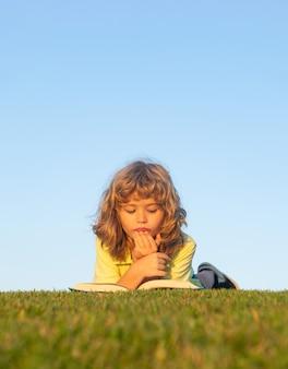 Gracinha lendo livro lá fora, na grama. escola ao ar livre, crianças aprendendo.