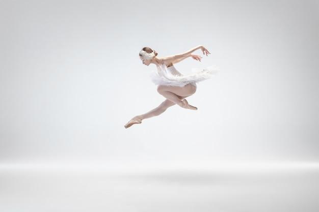 Graciosa bailarina clássica dançando isolada no fundo branco.