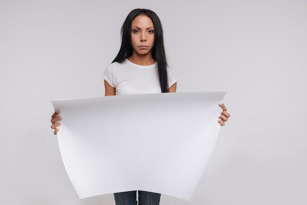 Graciosa e poderosa mulher segurando uma grande cantiga branca para campanha social e posando