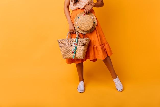 Graciosa garota bronzeada com bolsa de verão, posando no estúdio. despreocupada modelo feminino de saia longa, segurando o chapéu da moda.