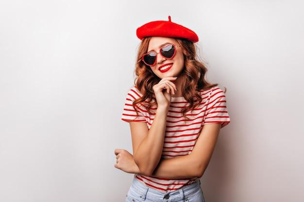 Graciosa garota caucasiana com cabelo ruivo sorrindo. linda jovem de boina vermelha, desfrutando da sessão de fotos.