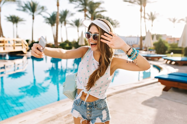 Graciosa garota dançando em pulseiras da moda e chapéu branco, fazendo selfie antes de nadar na piscina ao ar livre.