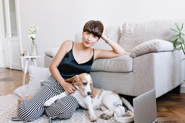 Graciosa garota de cabelos castanhos em um top preto relaxando no carpete perto de almofadas listradas e acariciando o filhote de cachorro beagle