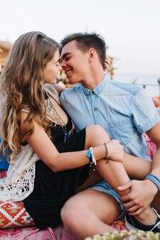 Graciosa garota de cabelos compridos em um elegante vestido preto abraçando suavemente seu lindo namorado, se divertindo em um encontro ao ar livre