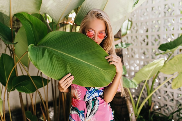 Graciosa garota loira usa óculos escuros elegantes se escondendo atrás de uma folha grande.