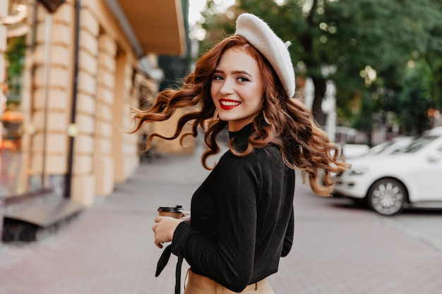 Graciosa garota ruiva de cabelos compridos olhando por cima do ombro. mulher bonita rindo na boina, apreciando o passeio.