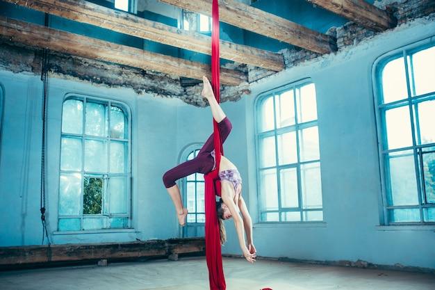 Graciosa ginasta fazendo exercícios aéreos com tecidos vermelhos em um antigo loft azul