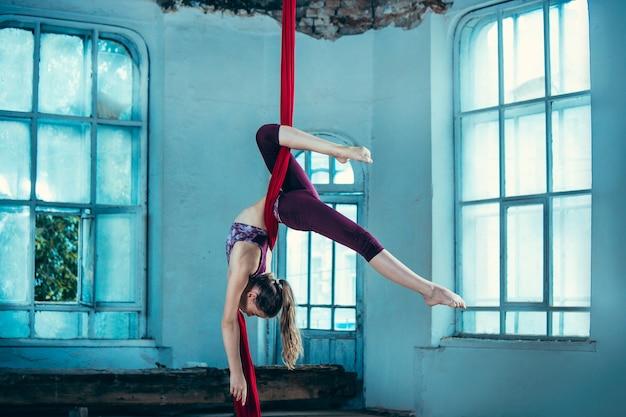 Graciosa ginasta fazendo exercícios aéreos no loft