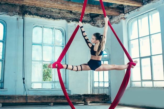 Graciosa ginasta realizando exercícios aéreos com tecidos vermelhos sobre fundo azul antigo loft. garota apta jovem adolescente caucasiana. o circo, acrobático, acrobata, artista, esporte, fitness, conceito de ginástica