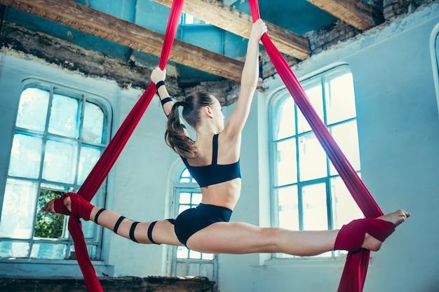 Graciosa ginasta realizando exercícios aéreos com tecidos vermelhos sobre fundo azul antigo loft. garota apta jovem adolescente caucasiana.
