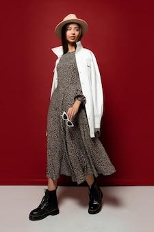 Graciosa modelo com chapéu da moda e jaqueta branca outono posando.