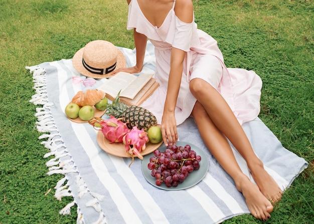 Graciosa mulher asiática desfrutando piquenique de verão no gramado verde perto da piscina.