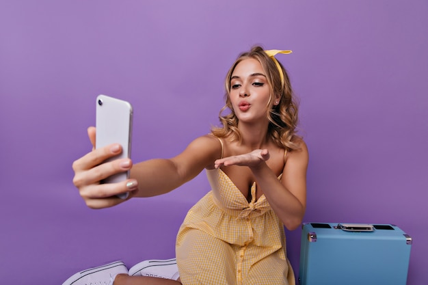 Graciosa mulher europeia fazendo selfie antes das férias. retrato interior de uma linda menina caucasiana com vestido amarelo, sentada perto de sua mala.