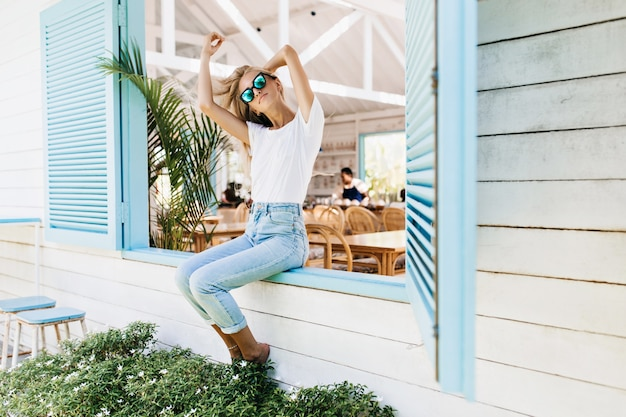 Graciosa mulher feliz sentada no parapeito da janela e brincando com seu cabelo loiro.