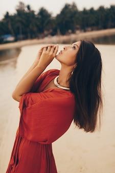 Graciosa mulher posando na praia, sentado na areia com vestido vermelho