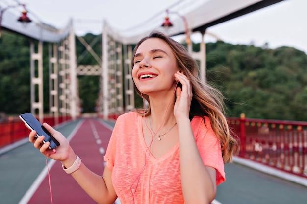 Graciosa senhora europeia ouvindo música favorita com os olhos fechados enquanto posava no estádio. garota fascinante em fones de ouvido relaxantes após a maratona.
