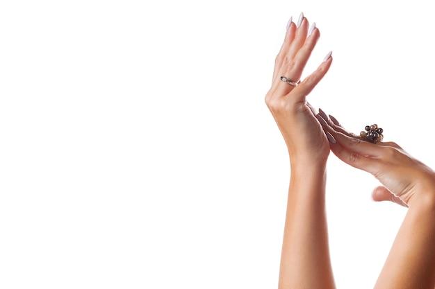 Graciosas mãos femininas com joias em um branco isolado