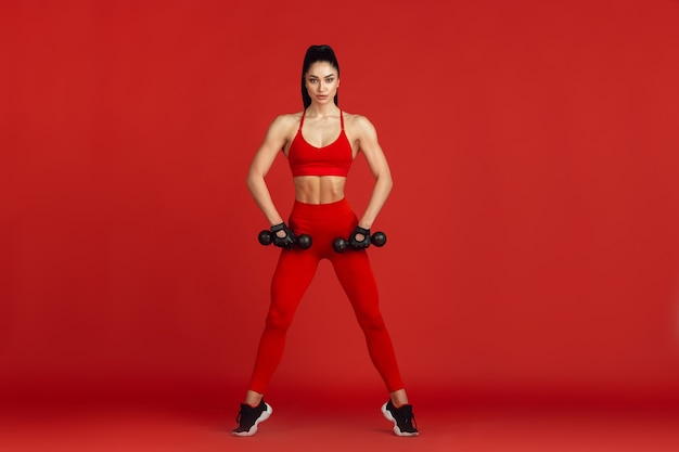 Gracioso. bela jovem atleta praticando em estúdio, retrato vermelho monocromático.