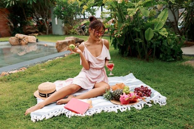 Gracioso modelo asiático sentado no cobertor, bebendo vinho e desfrutando de piquenique de verão no jardim tropical.