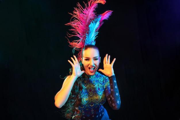 Gracioso. mulher jovem e bonita no carnaval, elegante traje de máscaras com penas em fundo preto em luz de néon. copyspace para anúncio. celebração de feriados, dança, moda. época festiva, festa.
