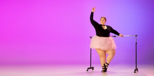 Gracioso, passageiro. bela modelo caucasiano plus size praticando dança de balé no fundo gradiente estúdio roxo-rosa em luz de néon. conceito de motivação, inclusão, sonhos e realizações.