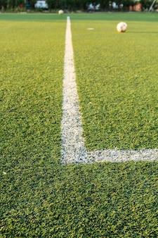 Grade branca do campo de futebol de relva artificial verde.
