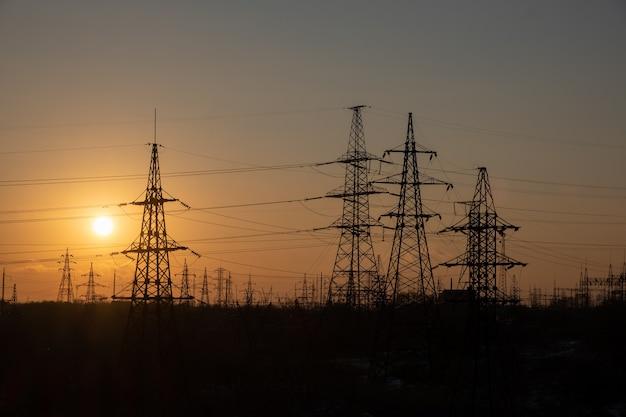 Grade linhas de alta tensão torre de alta tensão céu pôr do sol fundo