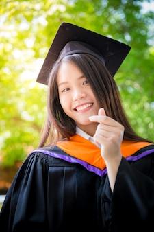 Graduação bonito asiática do retrato das mulheres com fundo verde da natureza, universidade de tailândia.