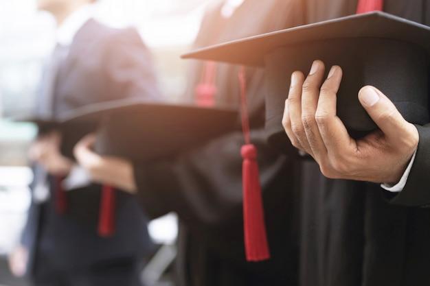 Graduação, estudante segura chapéus na mão durante os graduados de sucesso no início da universidade