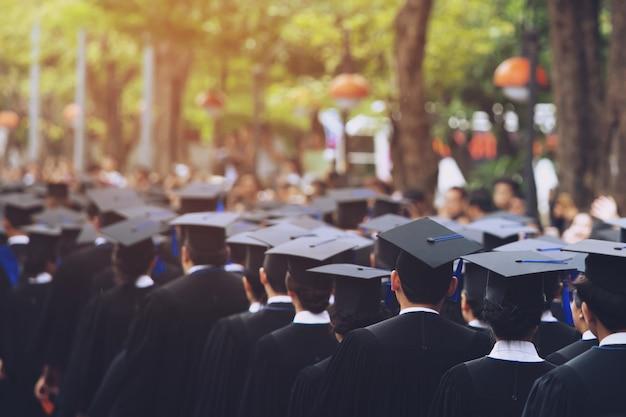 Graduação, o aluno segura chapéus na mão durante os graduados de sucesso de formatura da universidade, parabéns pela educação do conceito. cerimônia de graduação, parabenizou os formandos na universidade.