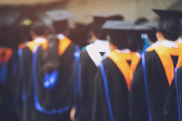 Graduação, o aluno segura os chapéus na mão durante os graduados de sucesso de formatura da universidade, parabéns pela educação do conceito