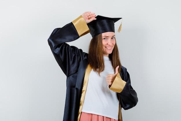 Graduada feminina aparecendo o polegar, mantendo a mão na cabeça em roupas casuais e uniformes e parecendo feliz, vista frontal.