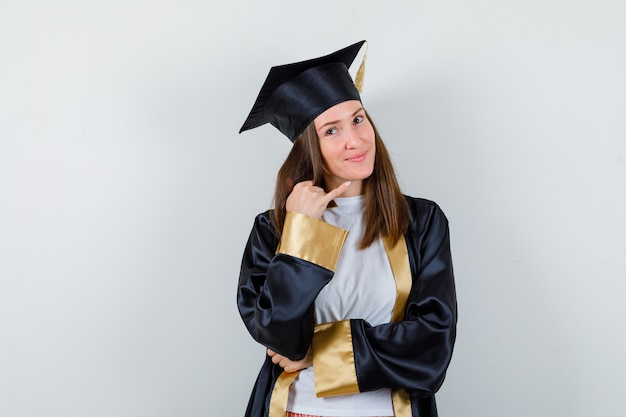Graduada feminina, apontando para o canto superior direito com roupas casuais e uniformes e parecendo esperançosa, vista frontal.