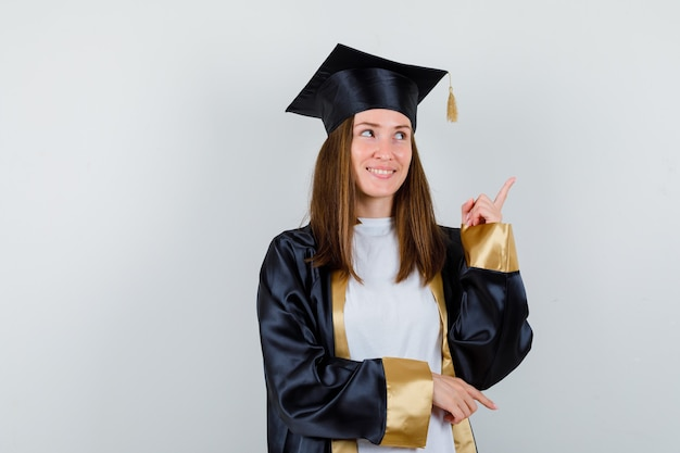 Graduada feminina com roupas uniformes e casuais, apontando para cima e olhando esperançosa, vista frontal.