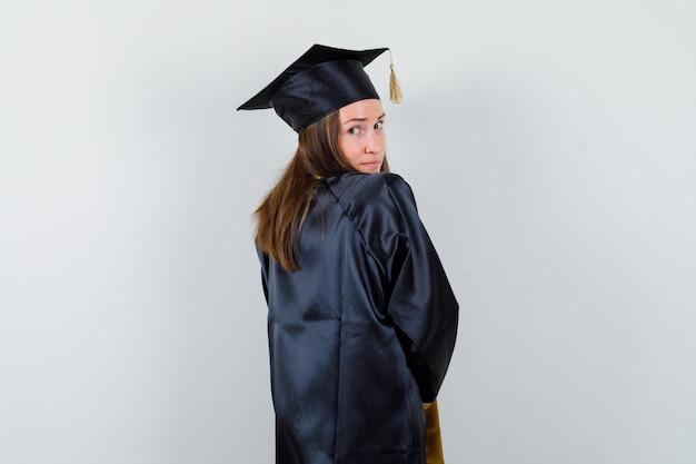 Graduada feminina em vestido acadêmico, olhando para a câmera por cima do ombro e bonito, vista traseira.