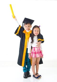 Graduado asiático da criança da escola no vestido e no tampão da graduação. tirando foto com a irmã e o irmão.