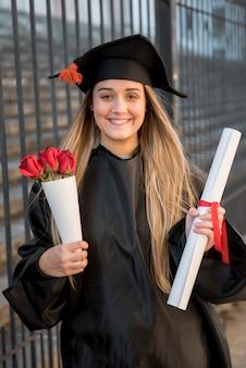 Graduado de vista frontal com buquê de rosas