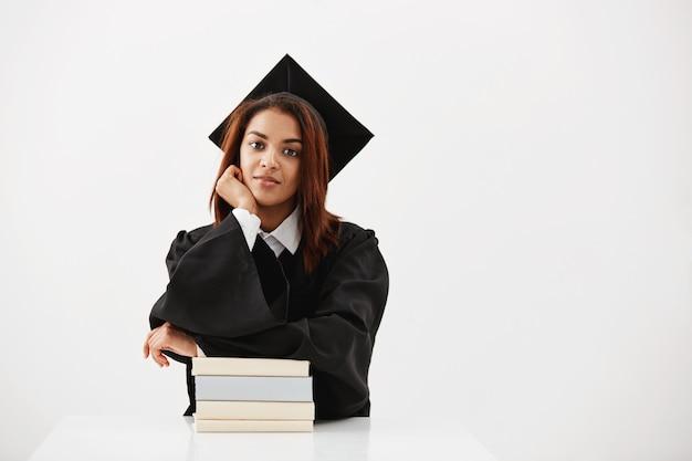 Graduado feminino africano em cap e manto sorrindo sentado com livros.
