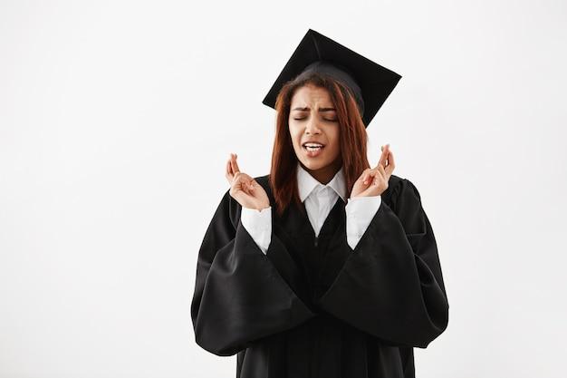 Graduado feminino africano no manto preto rezando sobre a superfície branca