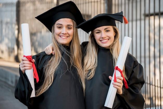 Graduados da faculdade sorrindo para a câmera